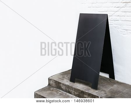 Blank mock up Sign stand on white wall Black Metal Board