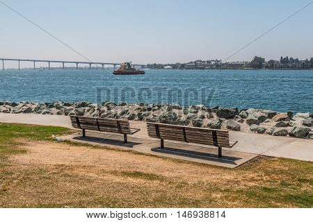 Two park benches at Embarcadero Park South in San Diego, California with the Coronado Bridge and a tugboat in the background.
