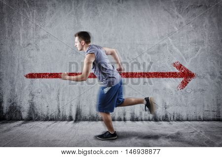 I walk my way. Young athlete running in the opposite direction . Running angaist the wall painted with an arrow in opposite direction.