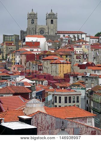 The roofs of Ribeira, one of the most ancient and authentic district of Porto, Portugal. In the background, the towers of the cathedral To do Porto. Photo taken in late afternoon clouds. The colorful houses stand out well on the gray sky. A rich image det