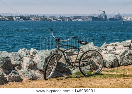 Bicycle at Embarcadero Park South in San Diego, California, with view of Coronado and military vessels in background