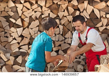 Boy helping his father stacking the firewood - handing him the pieces
