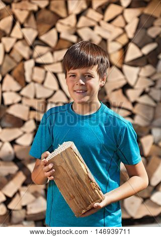 Boy stacking firewood - holding a piece and posing for the camera