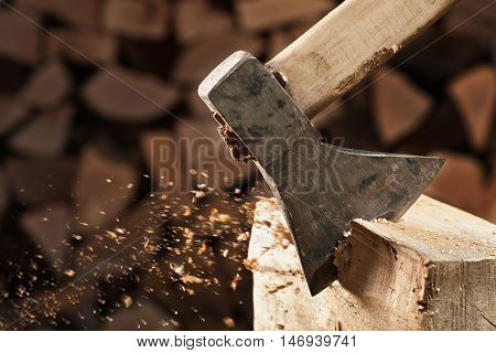 Closeup of axe cutting wooden block - with wood chips flowing in the air