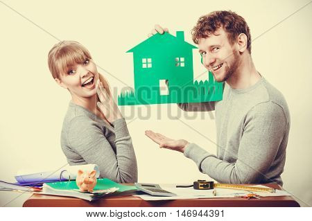 Finances property ownership real estate documents paperwork concept. Smiling couple preparing their future. Young girl and boy planning house for family.