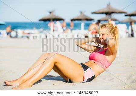 side view of smiling blonde athlete working out on beach