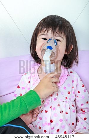 Sad asian child has bronchitis and crying. Kindly brother take care his sister with asthma problems making inhalation by mask at hospital. Happy family concept loving and bonding of sibling.