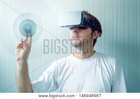 Man with VR goggles working in virtual reality environment casual male person using modern technology.