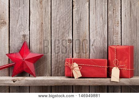 Christmas gift boxes in front of wooden wall. View with copy space for your text