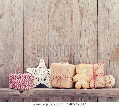 Christmas gift boxes and decor in front of wooden wall. View with copy space for your text. Toned