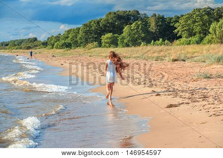 Young beautiful girl with long hair runs for the boy along the the seashore.