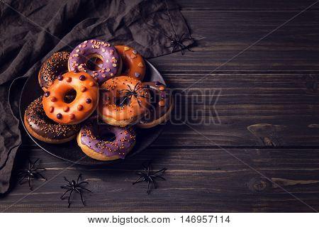 Halloween donuts on a dark wooden background