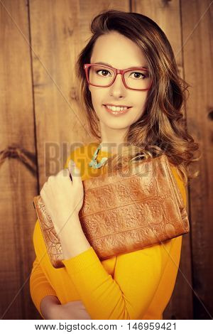 Pretty young woman in spectacles smiling at camera. Business woman. Bright colors.