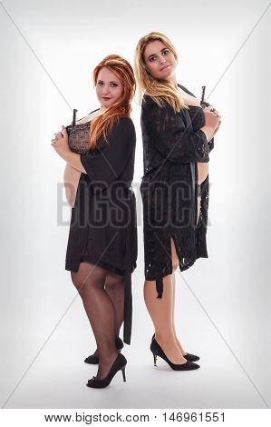 Red haired and Blonde curvy model in lingerie and negligee back to back with guns in hand. Studio Shot