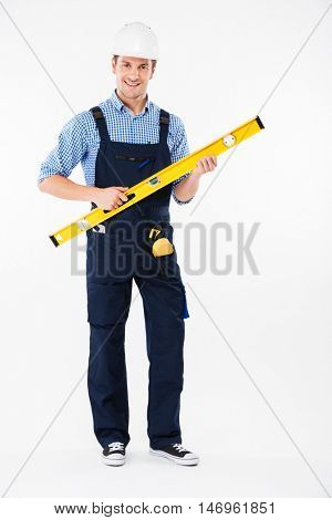Full length portrait of a concentrated young worker in overalls using level tool isolated on a white background