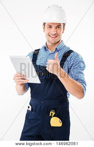 Happy male builder showing thumb up and holding pc tablet isolated on a white background