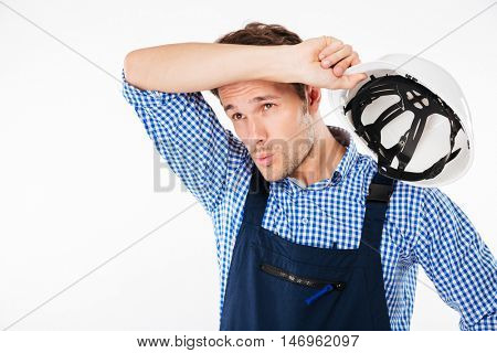 Portrait of tensed young constructor feeling exhausted after work isolated on a white background