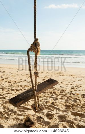 Cradle with sand beach and blue sea in blue sky background
