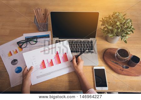Top view of young working woman using laptop and reading annual report document at work. Business woman working at her desk.