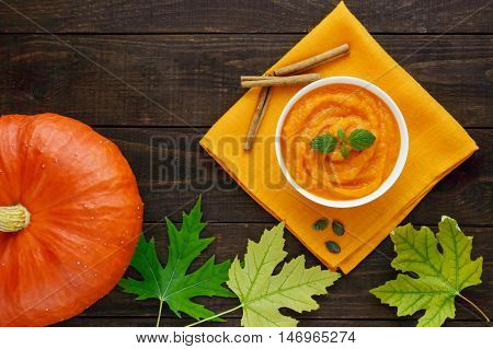 Organic pumpkin puree (soup) in a white bowl on dark wooden background. Dietary dish. Baby food. The top view