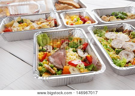 Healthy food and diet concept, restaurant dish delivery. Take away of fitness meal. Weight loss nutrition in foil boxes. Steamed veal with cous cous and vegetables at white wood