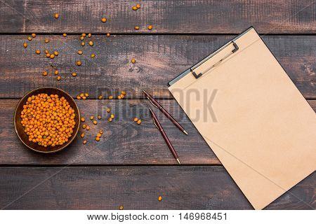 Office desk table with notebook, fresh sea buckthorn berries on wooden table