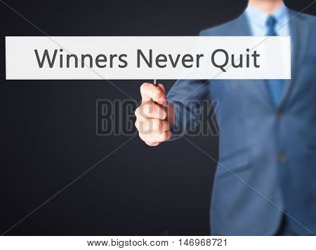 Winners Never Quit - Businessman Hand Holding Sign