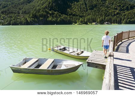 ALLEGHE,ITALY-AUGUST 22,2016:Children stroll near two moored boats on Lake of Alleghe in the Italian's Dolomite.