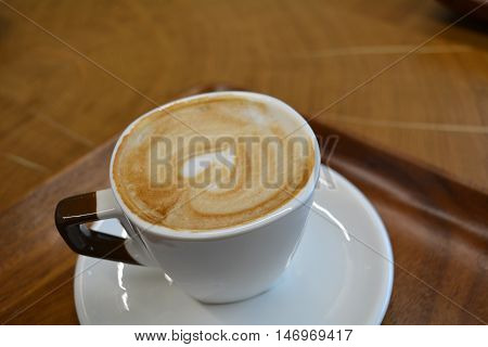 Delicious foamy cappuccino on a white cup on a plate
