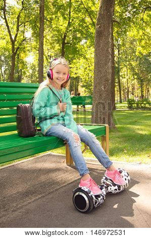 The Girl In Headphones Sitting On The Bench . She Has A Backpack. Her Legs Are On Segway .