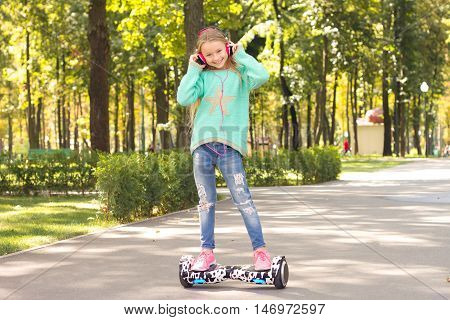 Girl rides on a self-balancing skateboard while wearting headphones . She is happy and smiling . A popular kind of electric transport