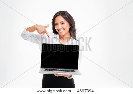 Smiling asian businesswoman pointing at laptop with blank screen isolated on the white background