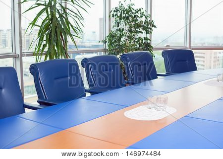 empty meeting room with blue chairs and a long table