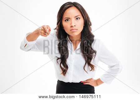 Portrait of a serious asian businessoman pointing finger at camera over white background