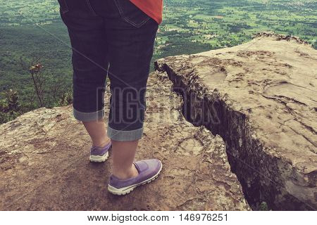 Closeup of tourist's feet on boulder at view point on summer day. Back view of woman hiking accomplishment on the top of the mountain travel on vacation. Motivation and freedom concept. Cream tone.
