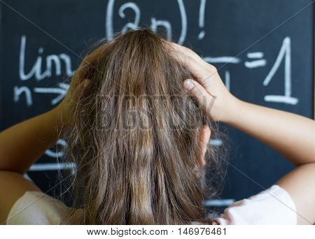 Schoolgirl thinks on the difficult task of mathematics on blackboard