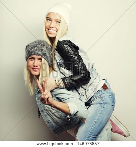 emotional, life style, happiness and people concept: Happy girl piggybacking with girlfriend. Studio shot over white background