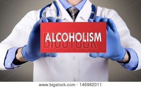 Doctor's hands in blue gloves shows the word alcoholism. Medical concept.