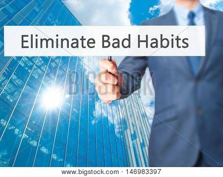 Eliminate Bad Habits - Businessman Hand Holding Sign