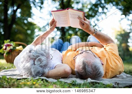 Senior Couple Resting At Park, Reading A Book