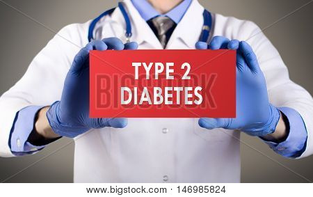 Doctor's hands in blue gloves shows the word type 2 diabetes. Medical concept.