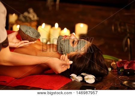Young woman lying on wooden spa bed. Massage and clay facial mask in spa salon. Girl on candles background in massage spa salon.