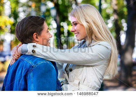 Young couple in love hugging and flirting in park and looking each other with love in autumn park.
