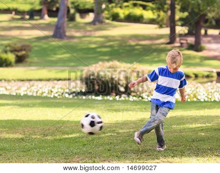 Boy Playing Football In The Park