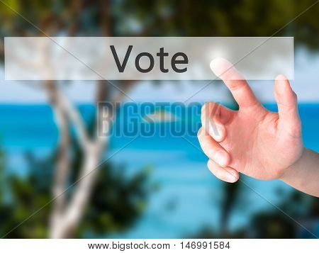Vote - Hand Pressing A Button On Blurred Background Concept On Visual Screen.