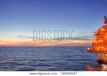 Sun set at the sea from offshore platform with warm light and lighting of platform.