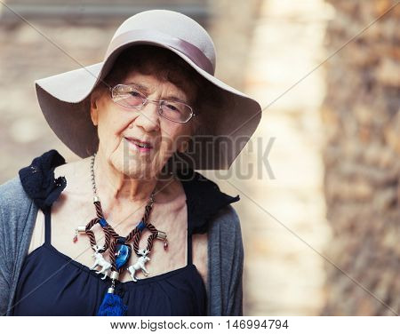 Stylish 90 years old woman walking around city. Granny female outdoors