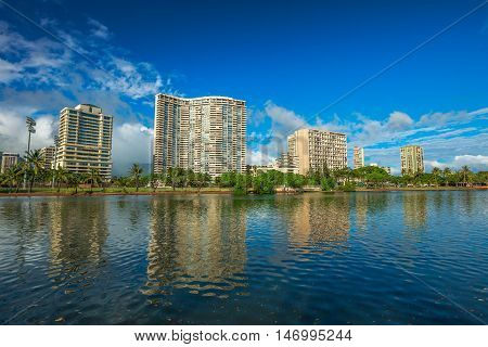Honolulu city skyline. Hotel and Honolulu skyscrapers reflected in the Ala Wai Canal in Oahu, Hawaii.