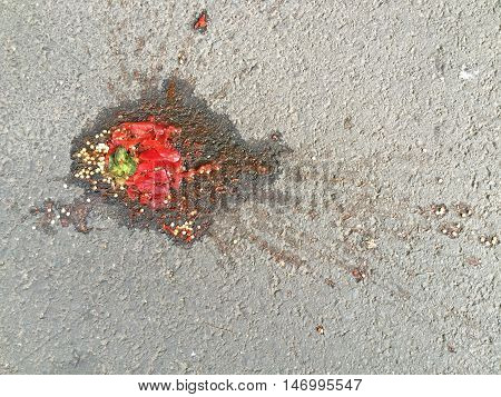 Squished red bell pepper on pavement background