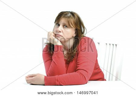 Portrait Of Sad Middle-aged Woman Sitting At A Table..